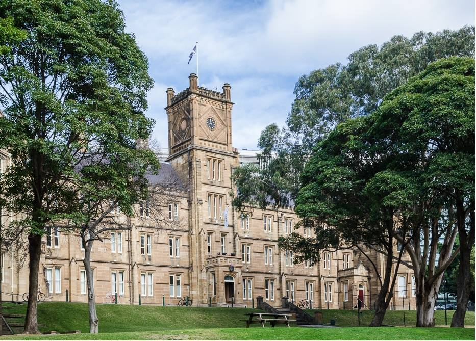 Main Building of St Andrew's College with flag flying, as pictured from The Glen near the College Oval.
