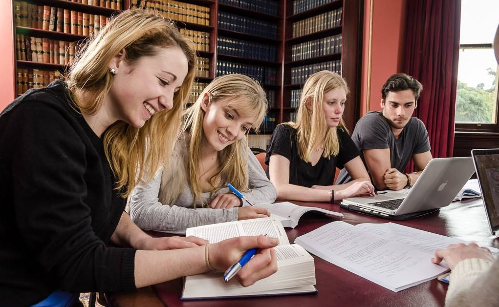 St Andrew's residents studying together at a table in the College Law Library