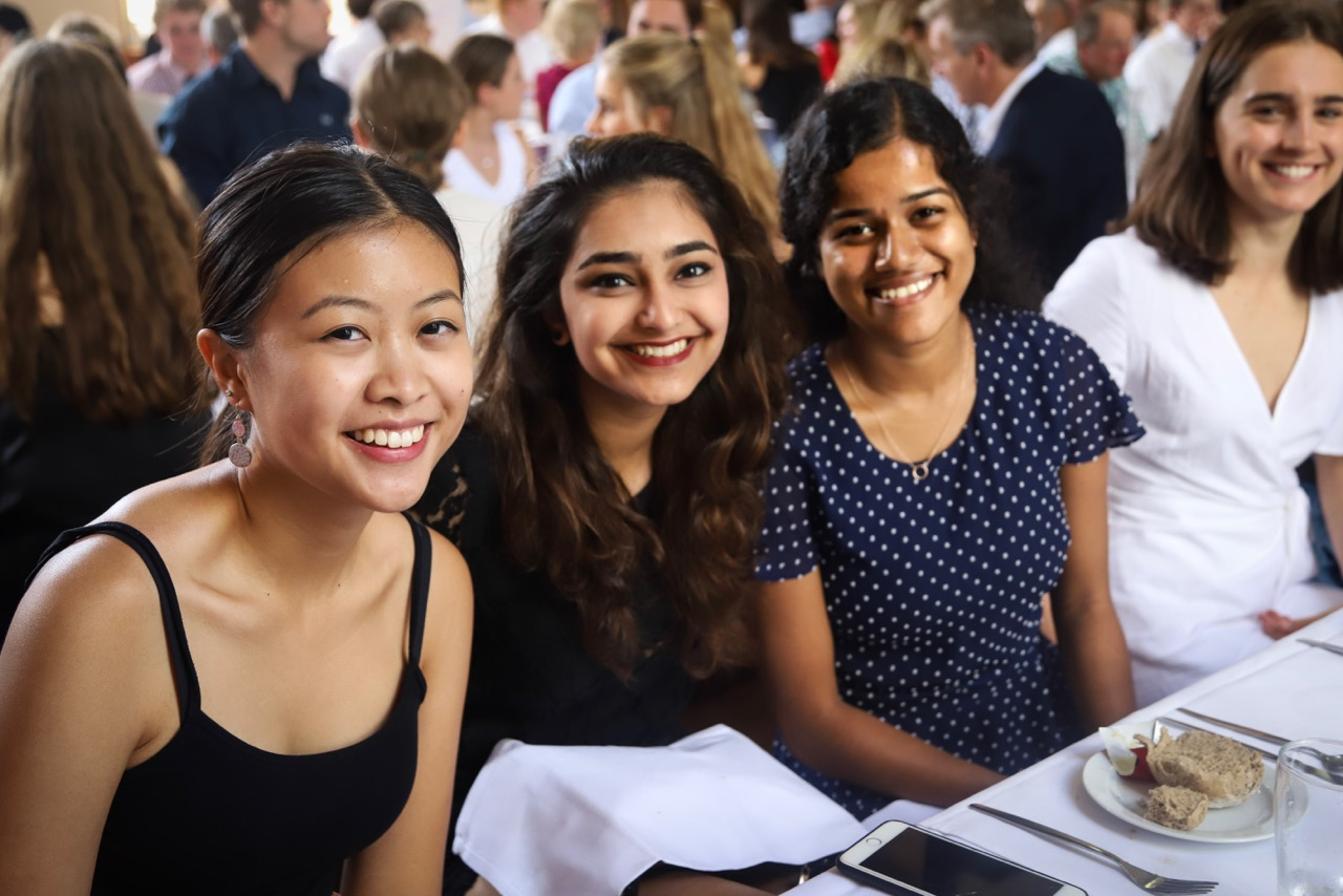 St Andrew's College women sitting together at a formal dinner event in the College's Dining Hall