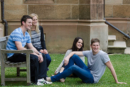 Male and female residents socialising together on a bench outside the Main Building overlooking The Glen.
